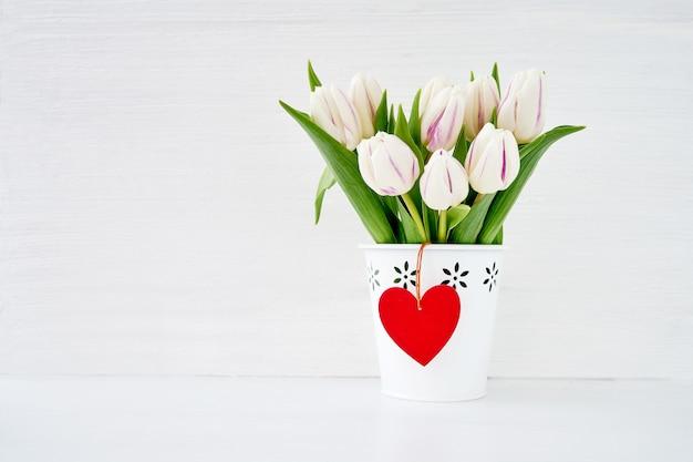 Ramalhete branco das tulipas no vaso branco com coração de madeira vermelho. conceito de dia dos namorados. copie espaço