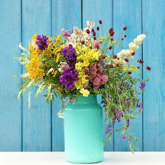 Ramalhete colorido brilhante de flores selvagens no vaso da lata de estanho do starm em placas de madeira azuis do fundo.