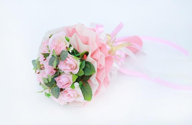 Ramalhete cor-de-rosa artificial das rosas isolado no fundo branco.