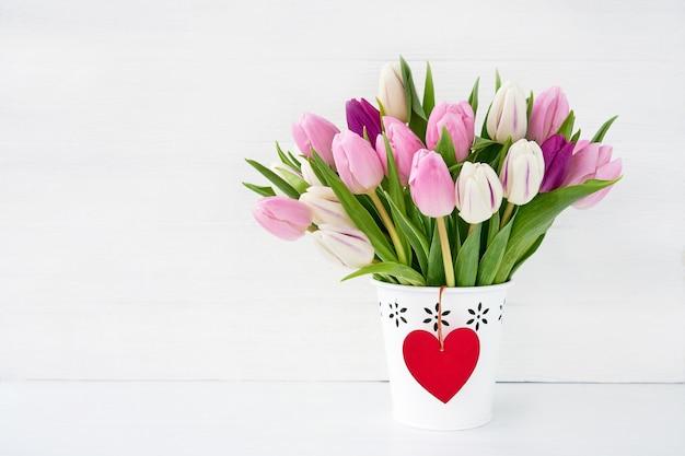 Ramalhete cor-de-rosa e branco das tulipas no vaso branco com coração vermelho. conceito de dia dos namorados. copie espaço