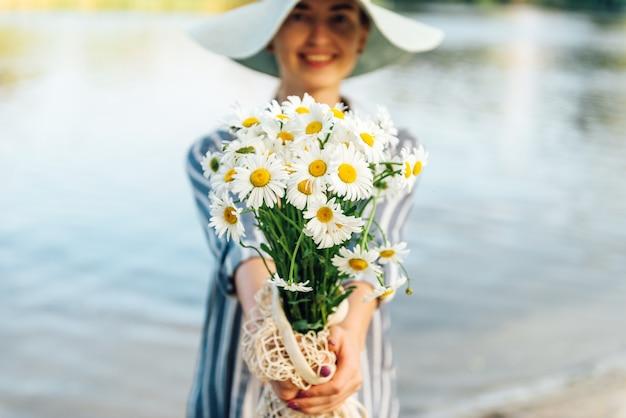 Ramalhete da camomila nas mãos da menina no rio. feliz, florista, conceito