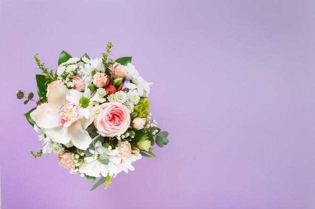 Ramalhete da flor com as caixas de presente no fundo roxo com espaço da cópia. vista plana leiga, vista superior floral dia dos namorados ou conceito de dia das mães