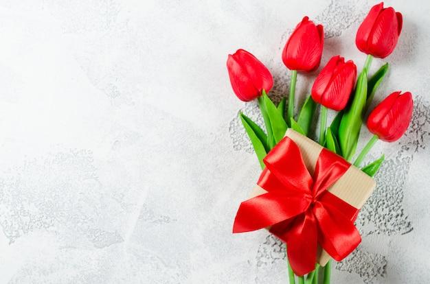 Ramalhete da mola de tulipas vermelhas e de caixa de presente.