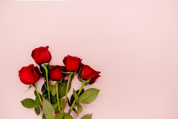 Ramalhete da rosa do vermelho das flores em um fundo cor-de-rosa.