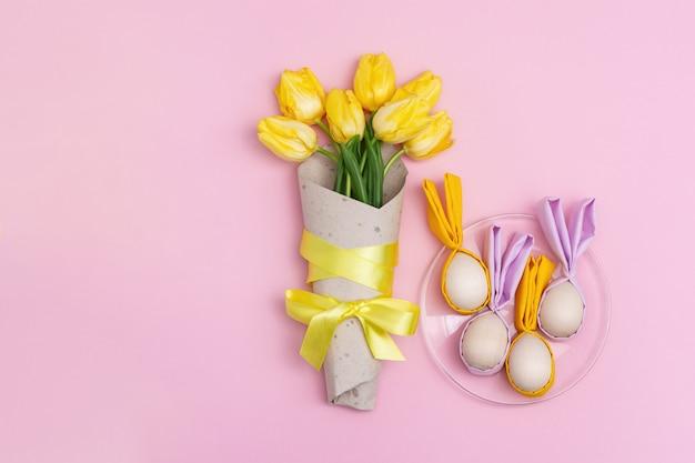 Ramalhete da tulipa amarela das flores e ovos da páscoa na placa, ovos da páscoa de madeira com as orelhas da tela como o coelho no rosa com espaço da cópia. vista plana leiga, superior.