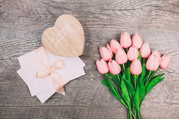 Ramalhete das tulipas e um envelope em um fundo de madeira, vista superior.