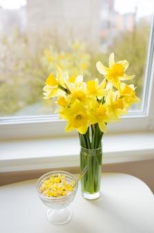 Ramalhete de narcisos amarelos amarelos brilhantes na tabela de madeira branca.