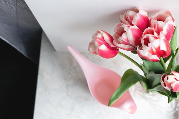 Ramalhete de tulipas cor-de-rosa e de vista superior do potenciômetro molhando em casa, interno. lindas flores, estilo de vida. parabéns de férias, vertical