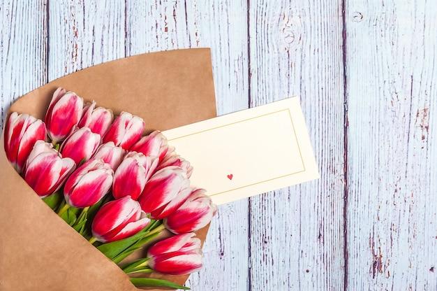 Ramalhete de tulipas vermelhas para o dia das mulheres do feriado e dia de são valentim no fundo de placas de madeira.