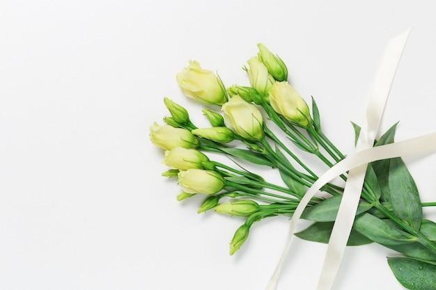 Ramalhete do botão branco não florescido fresco nas flores em uma luz com espaço da cópia. buquê de rosas brancas jovens com fita. vista do topo.
