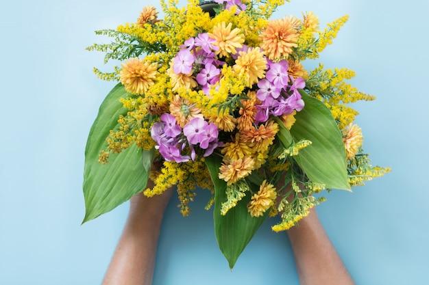 Ramalhete do outono de wildflowers amarelos na mão fêmea no azul.