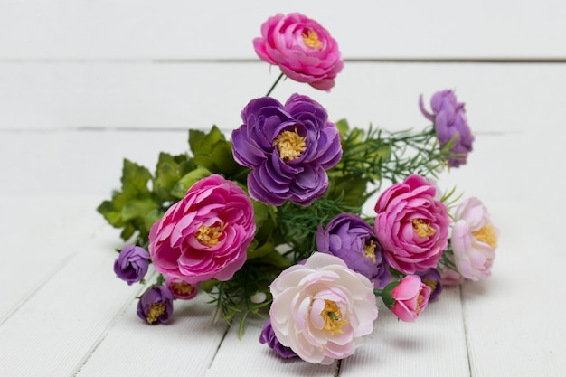 Ramalhete falsificado das flores isoladas em um fundo branco.