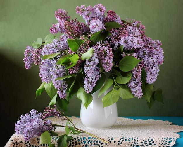 Ramalhete luxúria do lilás roxo em um vaso em uma tabela com uma toalha de mesa do laço.