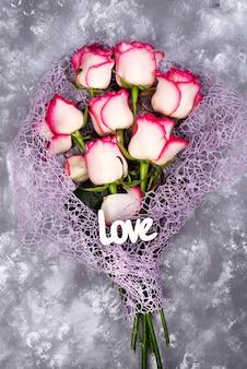 Ramalhete vermelho da flor da rosa do branco e amor da rotulação na tabela de pedra.