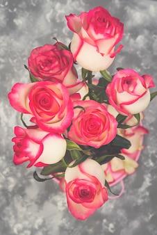 Ramalhete vermelho da flor da rosa do branco na tabela de pedra.