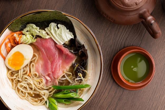 Ramen asiático com atum e macarrão e chá matcha em um restaurante