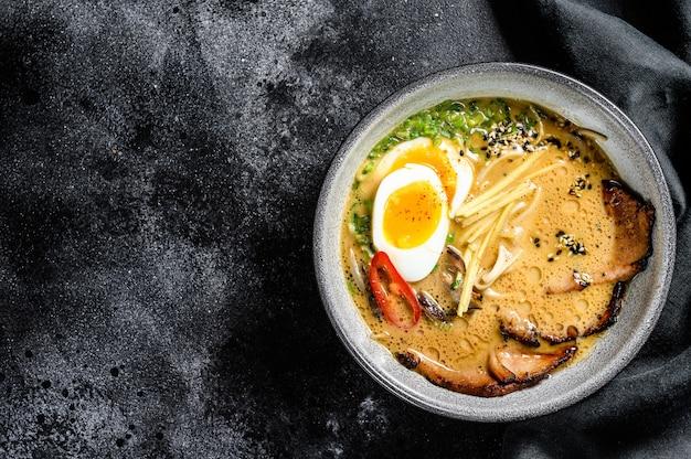 Ramen de sopa japonesa tradicional com caldo de carne, macarrão asiático, algas, carne de porco fatiada, ovos. fundo preto. vista do topo. copie o espaço