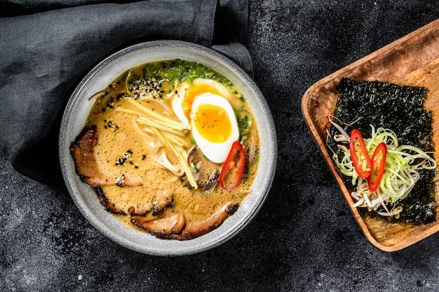 Ramen de sopa japonesa tradicional com caldo de carne, macarrão asiático, algas, carne de porco fatiada, ovos. fundo preto. vista do topo