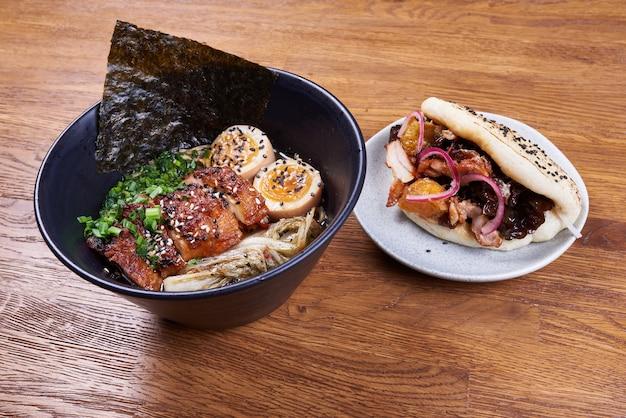 Ramen de sopa tradicional japonesa, macarrão, frango fatiado, ovos e um bao com frango, molho, cebola e sementes de gergelim.