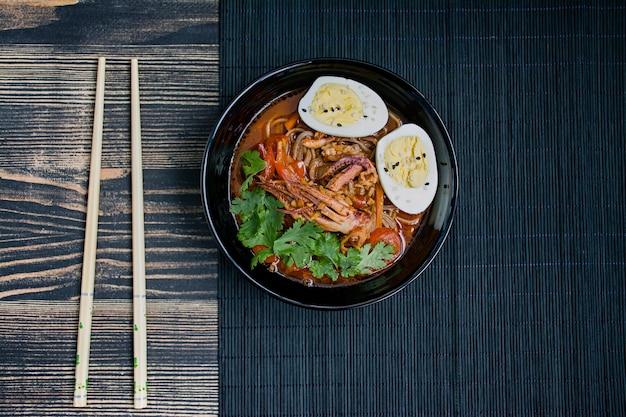 Ramen japonês com frutos do mar, ervas e ovos em conserva em uma superfície escura