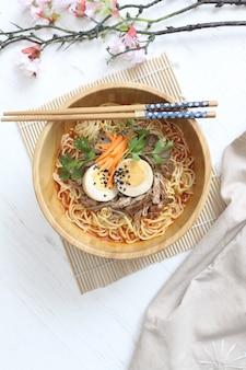 Ramen quente delicioso com ovo e carne na tigela de madeira com pauzinho