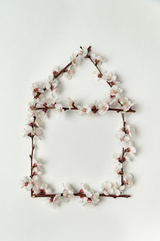 Ramifique com flores brancas em forma de casa em fundo branco.