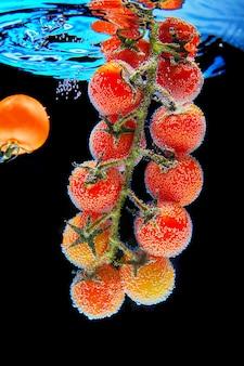 Ramifique com tomate cereja vermelho com folhas verdes cobertas com bolhas de gás de água mineral, um tomate caindo. fundo preto