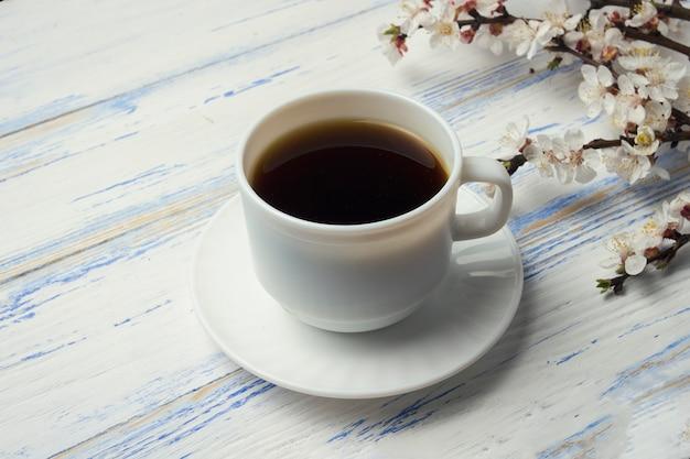 Raminho de cerejas com flores e copo branco com café preto sobre um fundo branco de madeira.