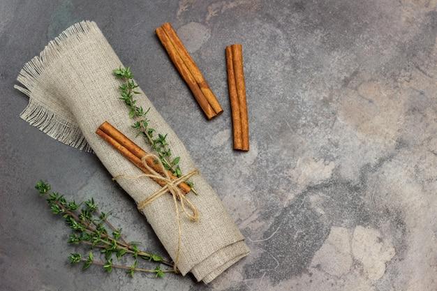 Raminho de tomilho e pau de canela no guardanapo de linho. raminhos de tomilho e paus de canela na mesa.