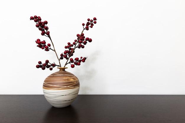 Raminhos com bagas em um vaso em uma mesa de madeira marrom