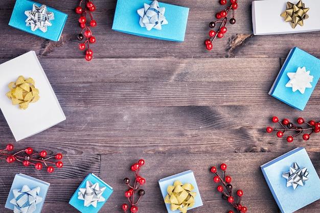 Raminhos com bagas vermelhas, pequenas caixas brancas e azuis com laços.