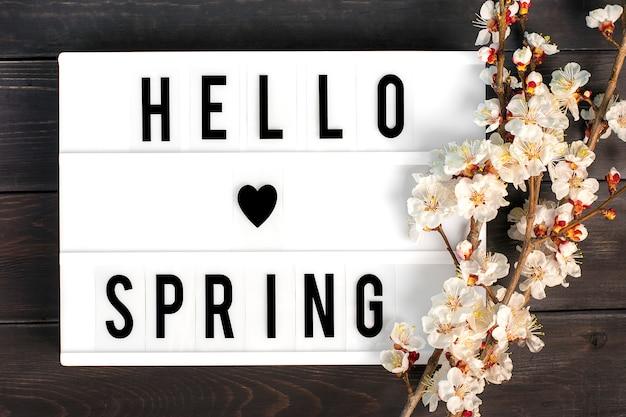 Raminhos da árvore de damasco com flores, mesa de luz com citação olá primavera