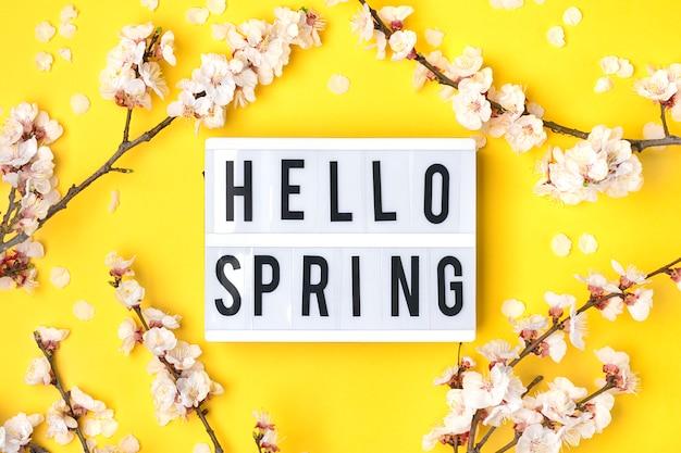 Raminhos da árvore de damasco com flores, mesa de luz com texto olá primavera