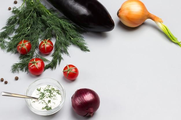 Raminhos de endro e tomate cereja molho em tigela de vidro duas cebolas na mesa