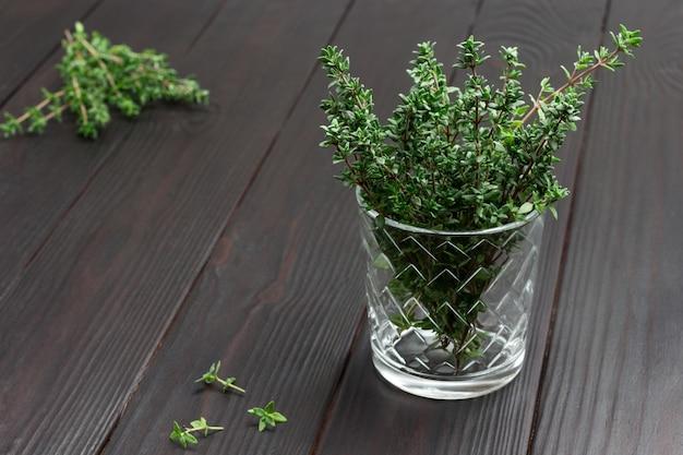 Raminhos de tomilho em vidro. tomilho na mesa. vista do topo. copie o espaço
