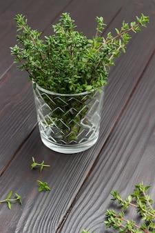 Raminhos de tomilho em vidro. tomilho na mesa. vista do topo.