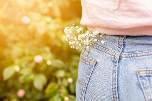 Ramo, com, flores brancas, colocado, em, bolso traseiro, de, calça jeans mulher