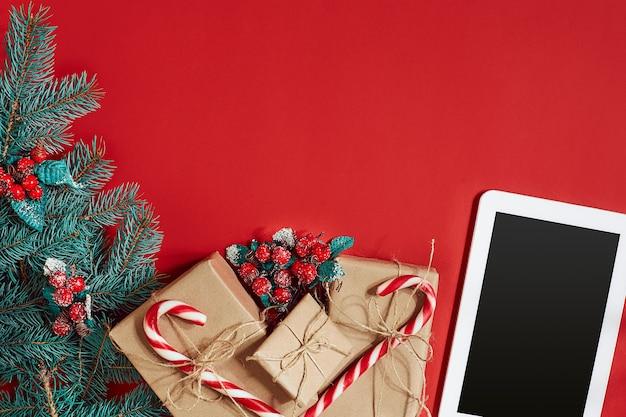 Ramo de abeto, caixa de presente e tablet branco com tela preta sobre fundo vermelho. vista do topo. postura plana. copie o espaço. ainda vida. natal e ano novo