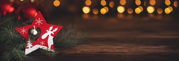 Ramo de abeto com bolas e luzes festivas no fundo de natal com brilhos.