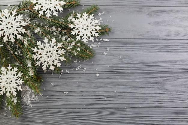 Ramo de abeto com neve de ornamento e flocos de neve de papel