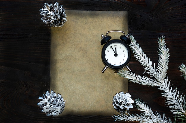 Ramo de abeto de natal com cones, 12 horas, assistir no fundo escuro de madeira, carta ao papai noel. copyspace