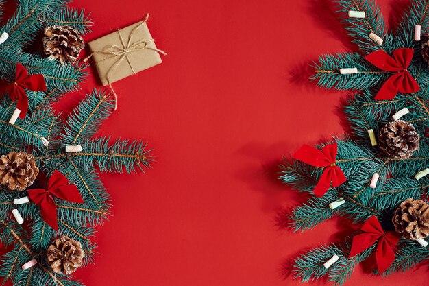 Ramo de abeto e caixa de presente em fundo vermelho. vista do topo. postura plana. copie o espaço. ainda vida. natal e ano novo