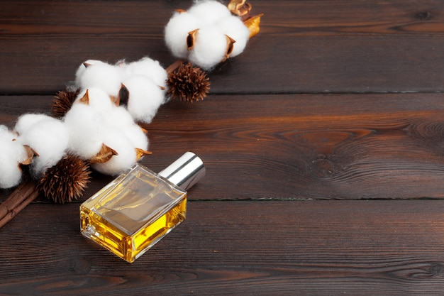 Ramo de algodão com frasco de perfume em fundo de madeira