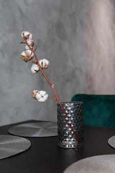 Ramo de algodão seco em vaso de cerâmica elegante fica na mesa da cozinha preta