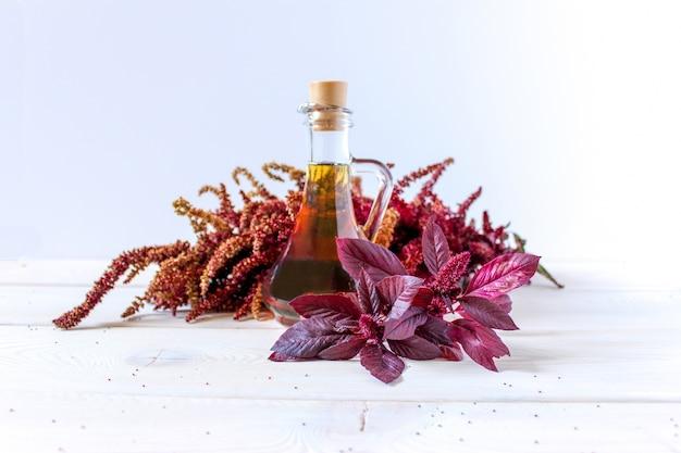 Ramo de amaranto vermelho com folhas e sementes, óleo em um navio. útil para a saúde, erva comestível.