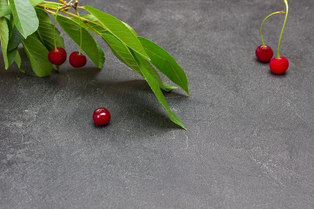 Ramo de cereja com frutas. bagas de cereja na mesa. copie o espaço. fundo preto. vista do topo.