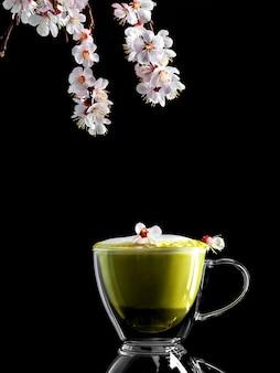 Ramo de cereja florescendo e uma xícara de chá verde matcha