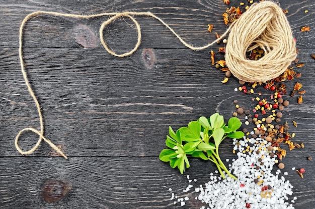 Ramo de feno-grego fresco com folhas verdes e flores brancas, sal, pimenta, sementes de feno-grego e um rolo de barbante contra uma placa de madeira preta