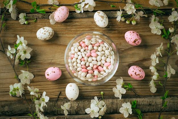 Ramo de flores da primavera e ovos de doces rosa coloridos para a páscoa no rústico