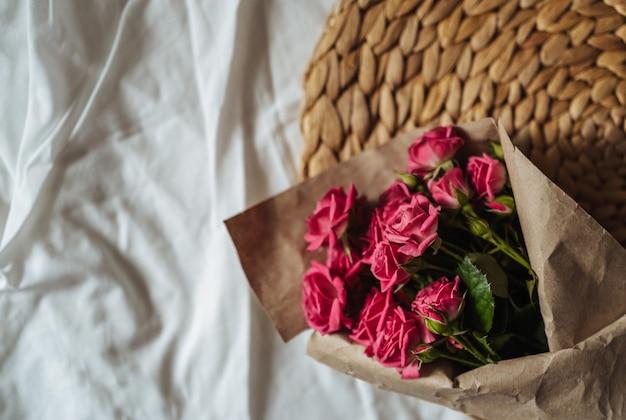 Ramo de flores da primavera e uma xícara de café em stan de palha